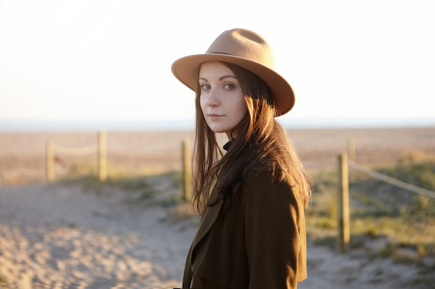 Outdoor portrait of stylish young european woman wearing trendy hat and black coat looking with subtle smile while having nice evening walk by the sea, dreaming and admiring sunset