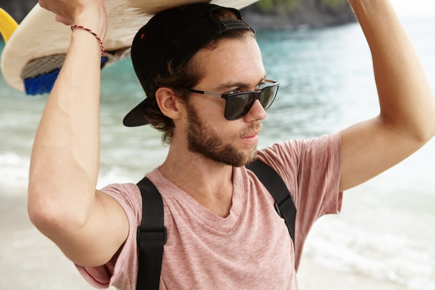 Outdoor portrait of stylish young surfer in sunglasses holding surfboard on his head and looking at blue sea with confident and determined expression