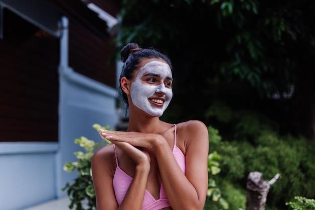 Ritratto all'aperto di pelle abbronzata calma donna abbastanza caucasica in bikini al centro benessere con maschera peeling bianca sul viso