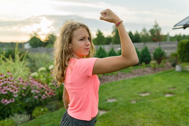 Outdoor portrait teenage girl flexing her muscles