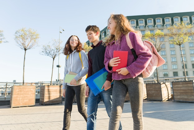 Outdoor portrait of teenage students with backpacks walking and talking.
