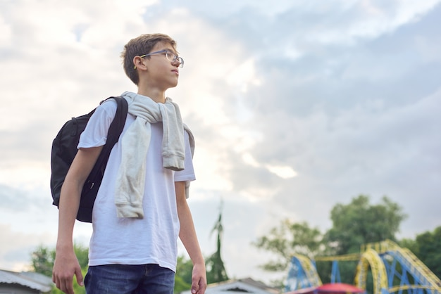 Outdoor portrait of teenager boy with glasses backpack