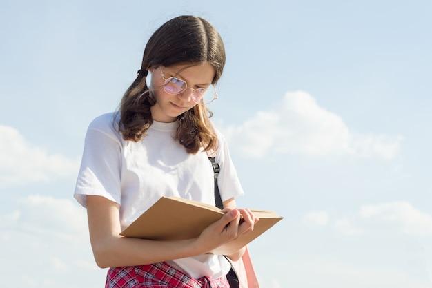 Outdoor portrait of teenager girl reading book