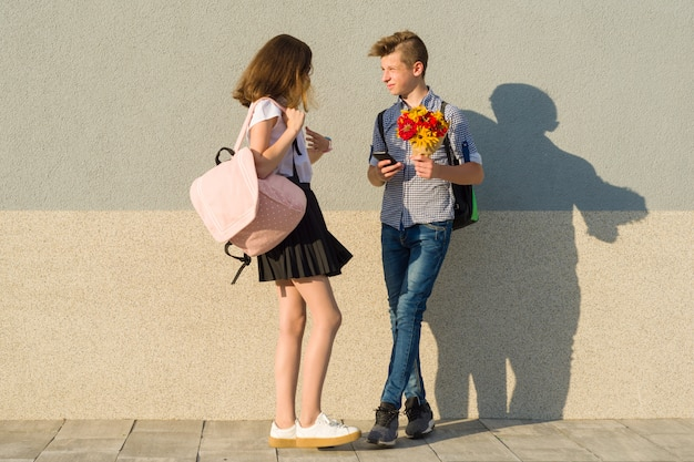 Outdoor portrait of teenagers, boy with bouquet of flowers and girl