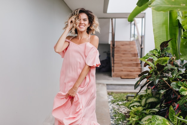 Ritratto all'aperto della ragazza caucasica alla moda che esprime emozioni positive vicino alle scale. piacevole modello femminile abbronzato in abito rosa ballando con un sorriso allegro.