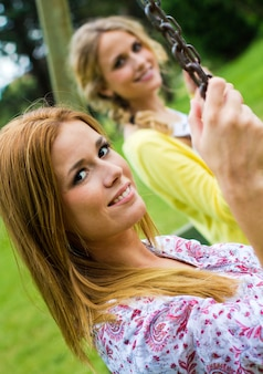 Outdoor portrait of two beautiful young womens posing at the park