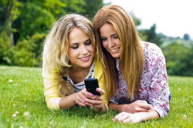Outdoor portrait of two beautiful young womens with mobile at the park