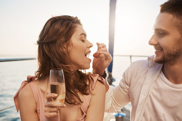 Outdoor portrait of two cute people in love, drinking champaign on a vacation, smiling and enjoying time on yacht. handsome bearded boyfriend feed girlfriend with strawberry. such moments are precious