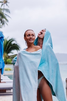 Outdoor portrait of two happy woman in bikinis with beach towels on vacation outside villa by swimming pool at rainy day