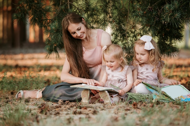 Outdoor portrait of two little girl is reading a book on the grass with mother.