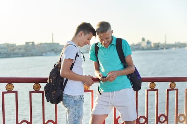 Outdoor portrait of two talking boys teenagers