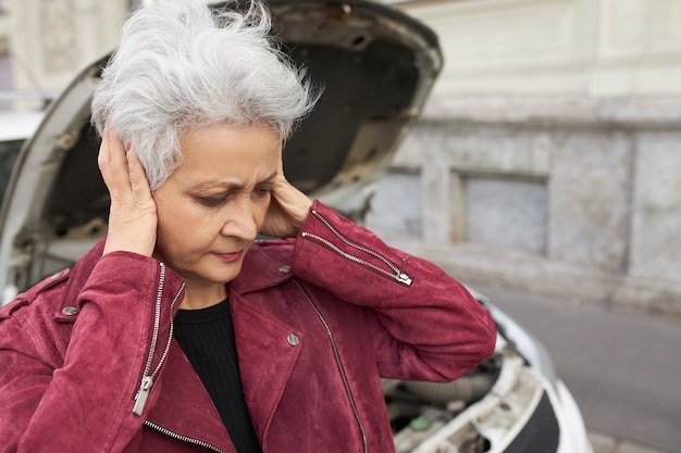 Outdoor portrait of unhappy stressed female pensioner with short gray hair covering ears, being frustrated because her car is broken