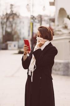 Outdoor ritratto di donna in cappotto invernale nero e sciarpa bianca in strada, tenendo il telefono cellulare.