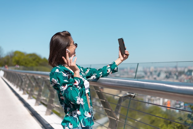 Outdoor portrait of woman in casual green shirt at sunny day stands on bridge looking on phone screen take selfie make video call wireless bluetooth headphones in ears