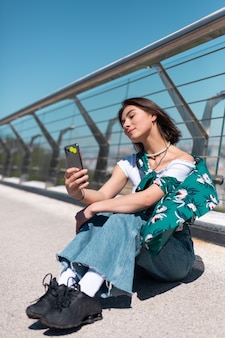 Outdoor portrait of woman in casual green shirt at sunny day stands on bridge looking on phone screen take selfie make video call
