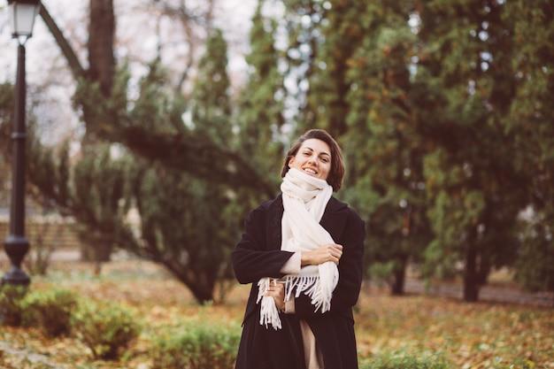 Outdoor ritratto di donna nel parco indossando cappotto nero invernale e sciarpa bianca