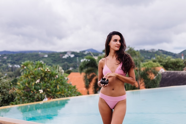 Outdoor portrait of woman in pink bikini at spa by swimming pool holding coffee scrab