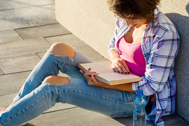 Outdoor portrait of woman reading book
