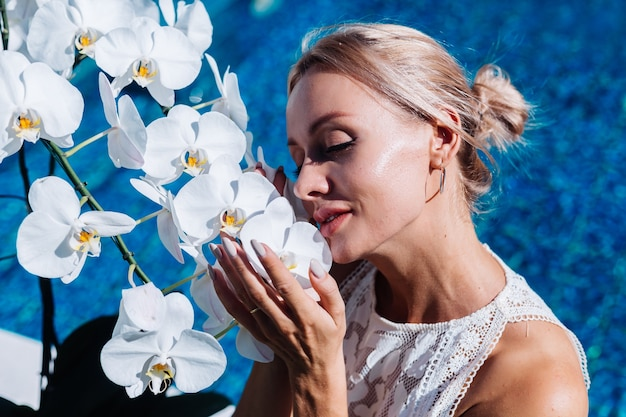 Outdoor portrait of woman in white wedding dress sitting near blue swimming pool with flowers orchid