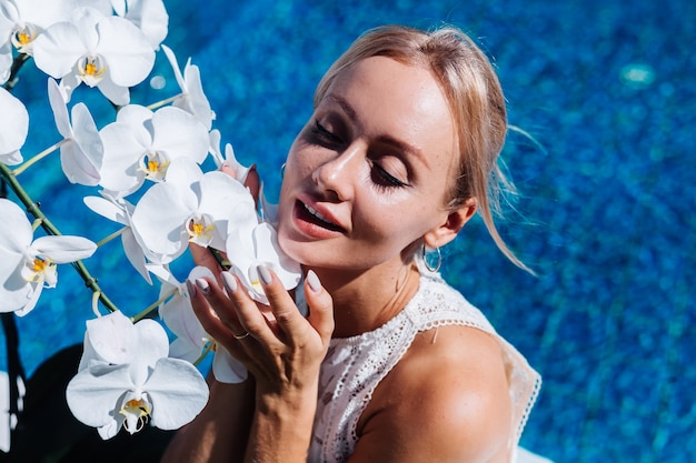 Outdoor ritratto di donna in abito da sposa bianco seduto vicino alla piscina blu con fiori di orchidea