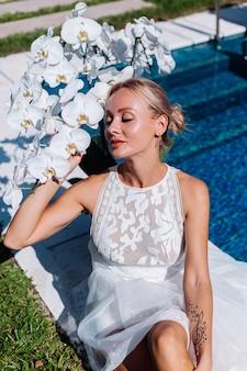 Outdoor ritratto di donna in abito da sposa bianco seduto vicino alla piscina blu con fiori
