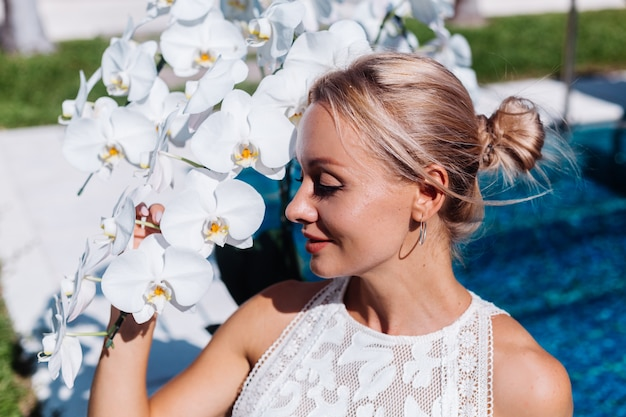 Outdoor portrait of woman in white wedding dress sitting near blue swimming pool with flowers