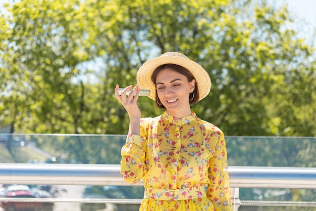 Outdoor portrait of woman in yellow summer dress and hat listen audio voice message on phone
