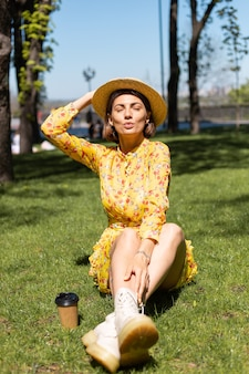 Outdoor portrait of woman in yellow summer dress and hat sitting on grass in the park