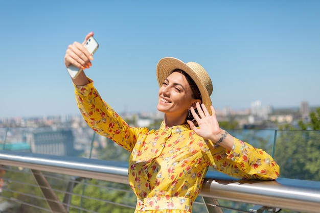 Outdoor portrait of woman in yellow summer dress and hat take selfie on phone, stands on bridge with city amazing view