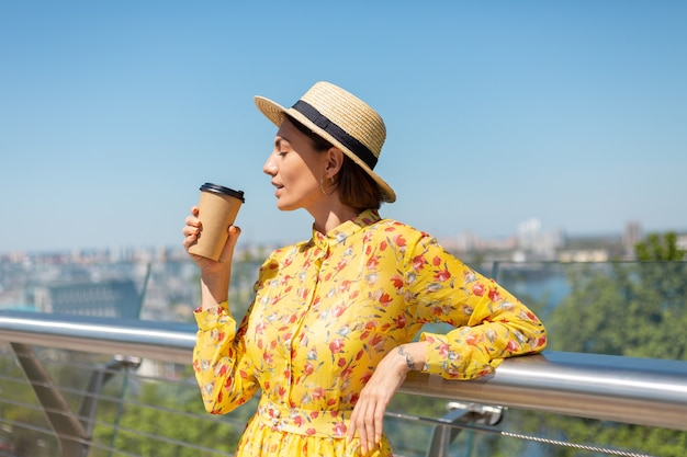 Outdoor portrait of woman in yellow summer dress and hat with cup of coffee enjoying sun, stands on bridge with city amazing view