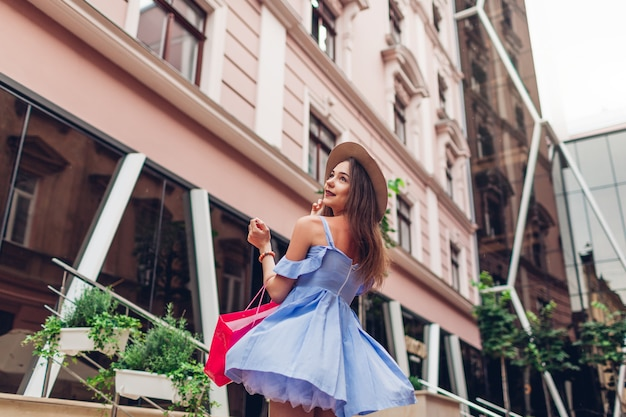 Outdoor portrait of a young beautiful fashionable woman dancing with shopping bag on city street