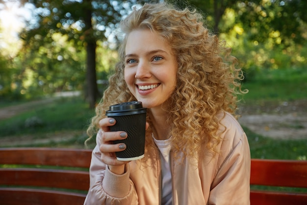 Outdoor portrait of young beautiful woman blonde sits on a park bench, drinking coffee