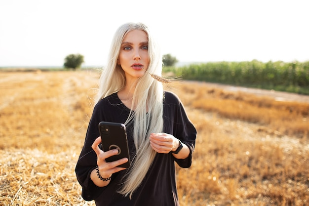 Outdoor portrait of young blonde girl with smartphone in hands, in fields.