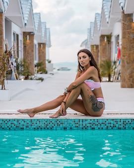 Outdoor ritratto di giovane indoeuropeo in forma abbronzata donna tatuata in bikini rosa carino