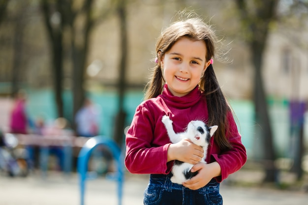 Outdoor portrait of young child girl with small kitten, girl playing with cat on natural