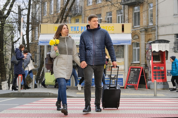 Outdoor portrait of young couple walking with suitcase on city