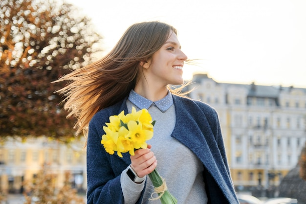 Outdoor portrait of young girl with bouquet of yellow spring flowers