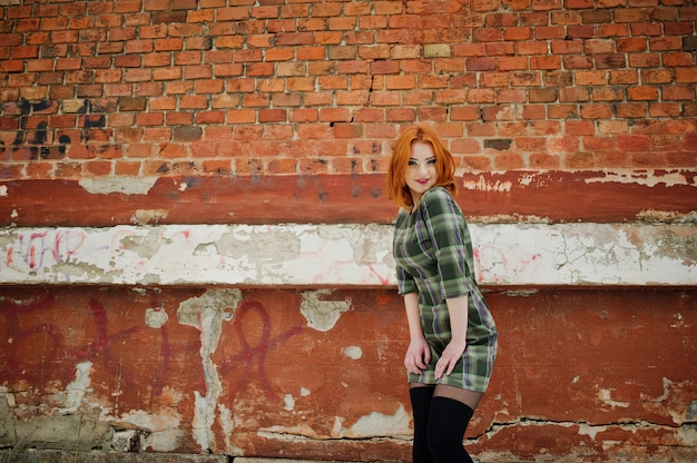 An outdoor portrait of a young pretty woman with red hair wearing checkered dress standing on the brick wall in winter day.