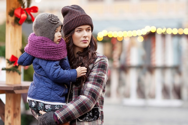 Outdoor portrait of young woman and little girl in christmas decoration in city