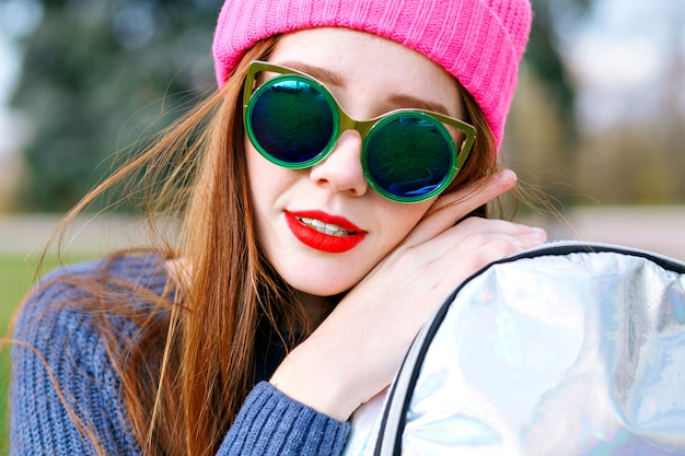 Outdoor positive fashion portrait of stunning beautiful ginger woman, posing at city park, wearing hipster hat and weather, trendy luxury sunglasses, youth, vacation, red lips, pastel colors.