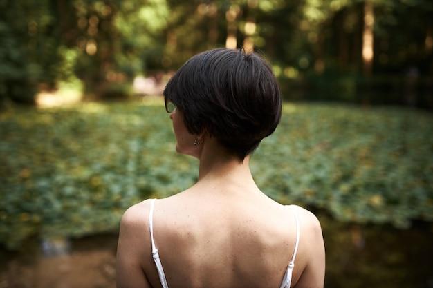 아름다운 야생의 자연에 감탄하는 짧은 머리를 가진 젊은 갈색 머리 여자의 야외 후면보기