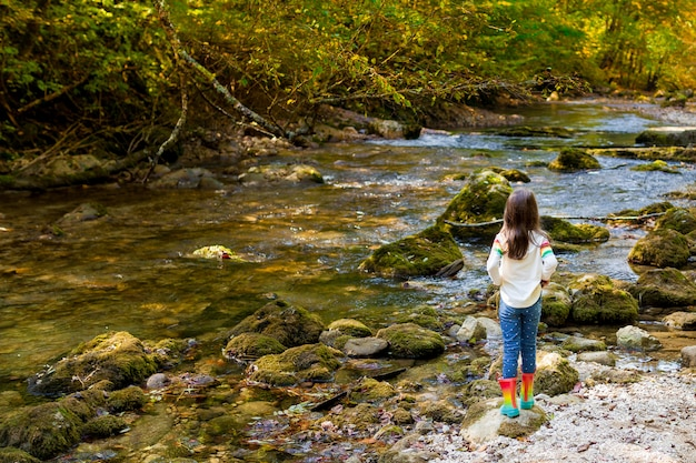 아이들과 함께하는 야외 레크리에이션과 멋진 모험. 어린 아이 소녀는 따뜻한 가을 날에 고무 장화에 숲에서 녹색 강을 따라 걷고있다
