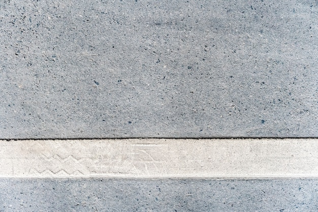 Outdoor road with white line marking on the bottom texture.