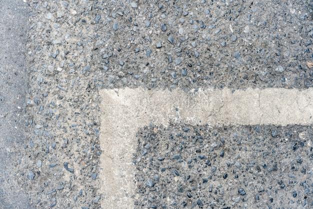 오른쪽 질감에 흰색 선 표시가있는 야외 도로.