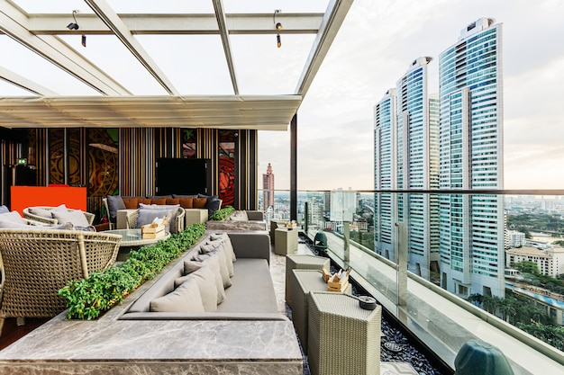 Outdoor rooftop bar with white movable roof and outdoor sofa