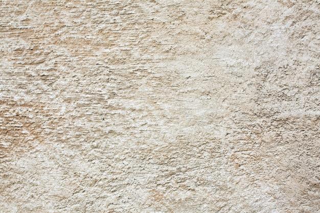 屋外の傷のあるベージュのコンクリートの壁。クローズアップショット