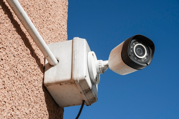 Outdoor security or surveillance camera installed on the exterior wall of a building. concept security, remote surveillance, surveillance.