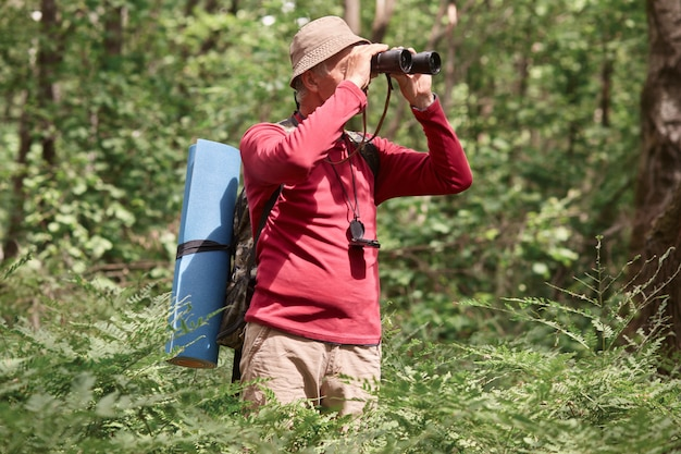 Outdoor shiot of man looking through binoculars in forest, senior traveller wearing casual clothing having adventure in wood, finding right way