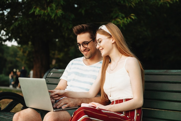 공원에서 벤치에 앉아 노트북 화면을보고 두 젊은 프로그래머의 야외 촬영. 사랑하는 커플 재미 밖에 서 웃 고.