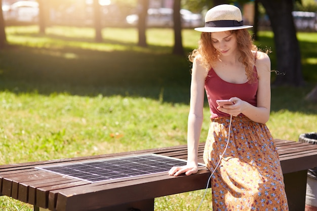 Outdoor short of attractive girl charges mobile phone via usb, charming female sitting on bench with solar panel in park. modern technology, ecology, alternative energy, public charging concept.